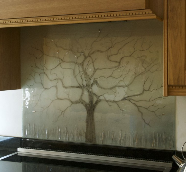 This beautiful, subtle and muted tree of life design showcases why even a relatively simple design beats plain old coloured glass splashbacks!