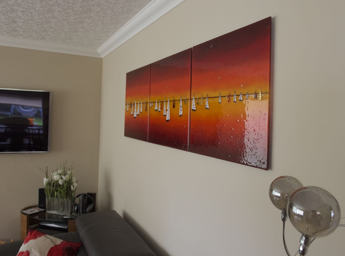 In the market for some glass wall art? This burning orange boat design is sure to be just the ticket!