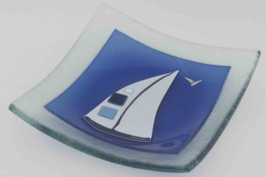 A beautiful fused glass art bowl with multiple layers, featuring a sail boat design.