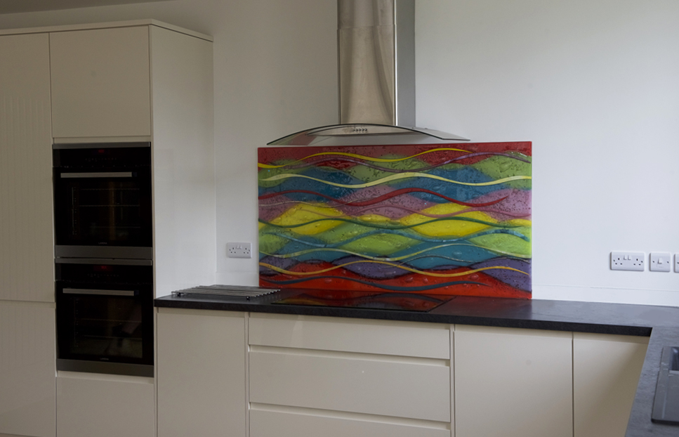 An example of one of our alternatives to coloured glass splashbacks. This fused glass art has a very colourful wave design!